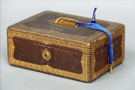 A Victorian tooled leather jewellery box The hinged rectangular lid with an inset brass loop handle,