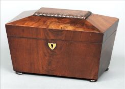 An early Victorian mahogany tea caddy Of sarcophagus form, the hinged cover enclosing twin lidded