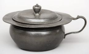 An 18th century pewter lidded chamber pot Of typical form, with loop handle, the cover with urn