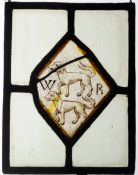 A 17th century stained and leaded glass panel The central lozenge decorated with a pair of dogs