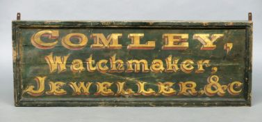 A 19th century painted wood watchmaker's sign Inscribed Comley, Watchmaker, Jeweller & C, on a green