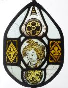 A 14th/15th century stained glass panel Of tear form centred with a portrait roundel of a saint,