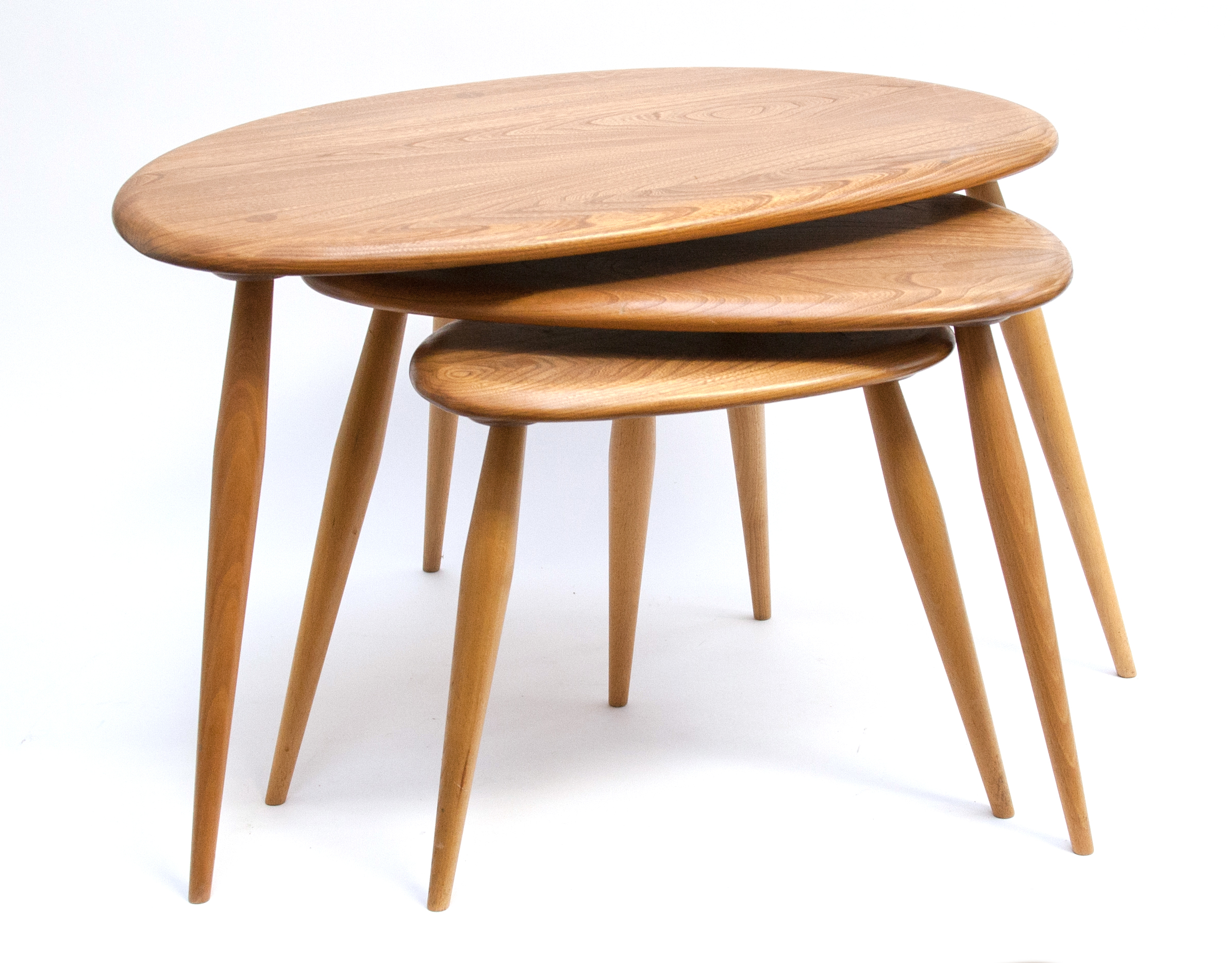 A nest of Ercol pebble tables, light elm and ash, 40cm high, 65cm wide