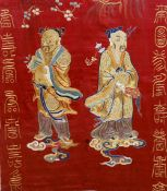 A 19th century Chinese embroidered silk panel The red ground panel centred with two deities atop