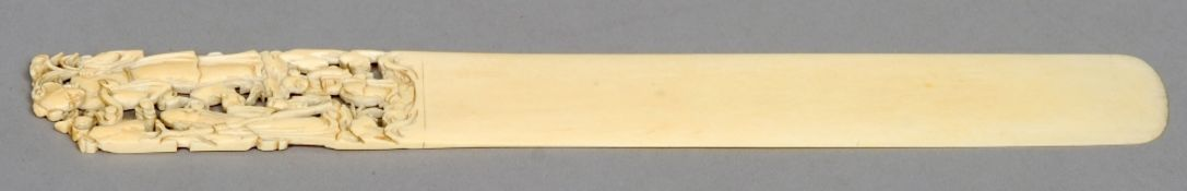 A Chinese carved ivory page turner The handle carved and pierced with figures.  31 cms long.