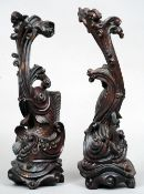 A pair of late 19th century Japanese carved hardwood models of carp Each carved amongst waves and