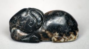 A Chinese pale and russet jade carving Modelled as a recumbent goat, possibly Song/Ming dynasty.
