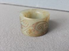 A Chinese carved jade archers ring With gilt scrolling decoration.  3.5 cms wide.   CONDITION