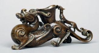 A Chinese bronze group Modelled as a dragon with an open vessel and further smaller dragon on his