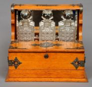 A Victorian oak games compendium/tantalus The mirrored upper section enclosing three glass decanters