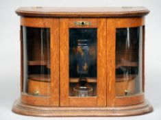 An oak smoker's cabinet The shaped hinged top above a glazed door flanked with a pair of bow