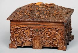 A 19th century Black Forest carved box Formed as a cottage with scrolling floral decoration.  21 cms