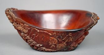 A Chinese carved horn libation cup The exterior decorated with a figure in a landscape and with