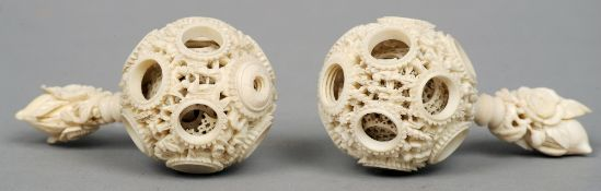 Two Cantonese carved ivory puzzle balls Each of typical form mounted on a florally carved handle.