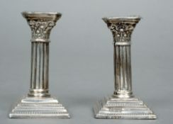 A pair of Edwardian miniature silver candlesticks, each hallmarked Birmingham, one 1902, the other