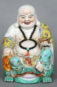 A Chinese porcelain figure of Buddha Modelled in a brightly coloured robe sitting astride a toad,