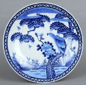 A Japanese blue and white charger  Decorated with a bird of prey perched in a tree.  46 cms