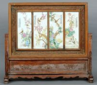 A Chinese porcelain inset carved hardwood screen The panels painted with birds amongst foliage and