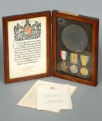 A leather cased trio of World War I medals, a death plaque and cap badge, awarded to 2nd Lt. Charles