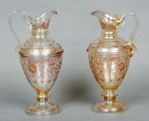 A pair of 19th century Venetian glass ewers Each clear glass body with tubular gilt decoration.