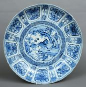 A large Chinese Kangxi blue and white charger The deep border decorated with panels of flowers and