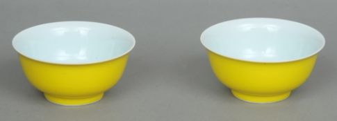 A pair of Chinese bowls Each exterior with a plain yellow ground, the underside with painted