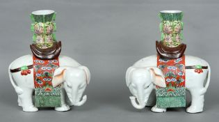 A pair of Chinese porcelain elephant form vases Each with lobed cylindrical necks above the white
