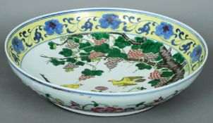 A large 19th century Chinese charger The rim with a thick yellow band decorated with blue floral