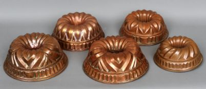 Five various copper pudding moulds Each of shaped domed form with a hanging ring.  The largest 29