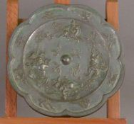 A Chinese white metal mirror Cast with figures playing polo within floral sprays opposing a polished