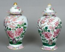A pair of Chinese famille rose vases and covers Each decorated with insects amongst blossoming
