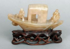 A Chinese carved jade boat Modelled with three figures, standing on a pierced carved hardwood base.
