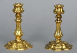 A pair of 19th century gilt bronze candlesticks Each with petal form base etched decoration and