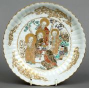 An 18th century Japanese plate The scalloped vessel with gilt heightened scholarly figures in a