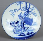 A Japanese porcelain blue and white charger Decorated with an exotic bird perched in a tree.  47 cms