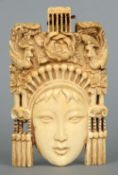 A 19th century Eastern ivory pendant Carved as a female face beneath birds and flowers.  14 cms