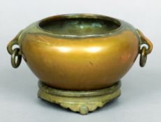 A Chinese bronze censor on stand Of typical circular bulbous form with twin ring and loop handles,