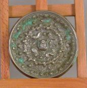 A Chinese white metal mirror Cast with various animal and bird figures opposing a polished surface.
