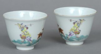 A pair of Chinese porcelain tea bowls Each decorated with a figure and a deer opposing stylised
