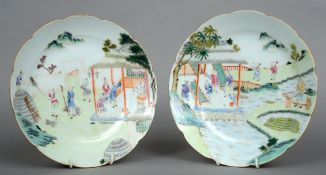 A pair of Chinese porcelain plates Each with lappet rim and decorated with various figures in a