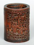 A 19th century Chinese carved bamboo brush pot Decorated with figures amongst a landscape, deer