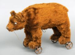 An early 20th century pull-along growling bear The plush covered body with glass bead eyes,