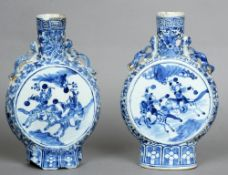A pair of 19th century Chinese blue and white moon flasks Each decorated with battling figures on