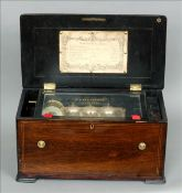 A 19th century rosewood cased music box The inlaid hinged rectangular top enclosing the cylinder