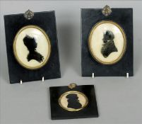 A pair of 19th century reverse painted silhouettes on glass Of a gentleman and his wife, framed;