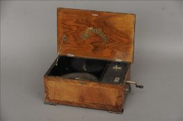 A 19th century walnut cased symphonium box The hinged rectangular lid centred with a transfer