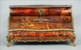 A 19th century ormolu mounted tortoiseshell table top stationery cabinet Of bombe form, the