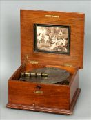 A 19th century walnut cased polyphone The moulded hinged top centred with a marquetry panel, the lid