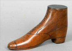 A 19th century treen snuff shoe Of typical carved laced design with a swivelling bronze lid. 16