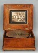 A large 19th century walnut cased polyphone The moulded hinged top inset with a marquetry panel, the